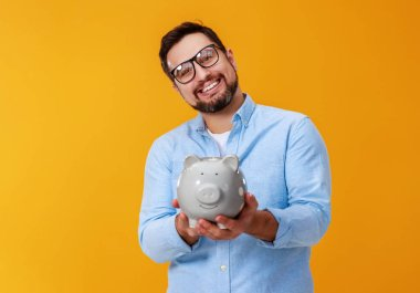 concept of Finance and business.  man with  piggy Bank on  yello