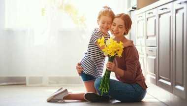 happy mother's day! child daughter   gives mother a bouquet of f