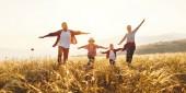 Fotografie glückliche Familie: Mutter, Vater, Kinder Sohn und Tochter in der Sonne