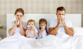 Erkältungen und Viruserkrankungen. Familie mit Schnupfen und Fieber im Bett