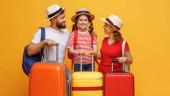 Optimističtí rodiče a dcera opírající se o zavazadla a usmívající se na kameru během letních prázdnin proti žlutému pozadí