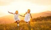 šťastné děti sestry dvojčata dívky v bílých šatech běh při západu slunce v přírodě v létě