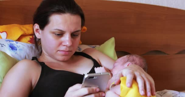 Stillende Mutter mit Smartphone