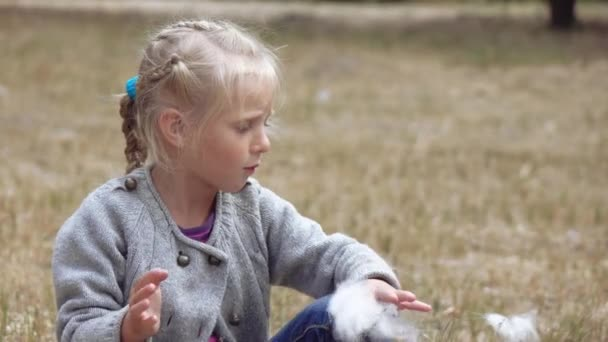 Girl child blowing fluff of bulrush