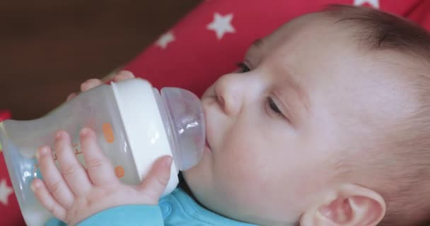 Child learns to drink from a bottle