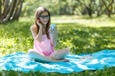 Girl lay down or relaxing on green grass listening music with smartphone in summer or spring