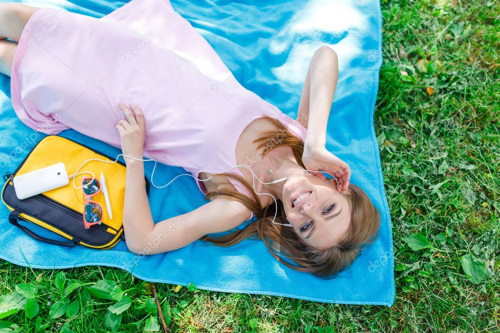 Woman relaxing on the grass in a park listening to music on her mobile phone