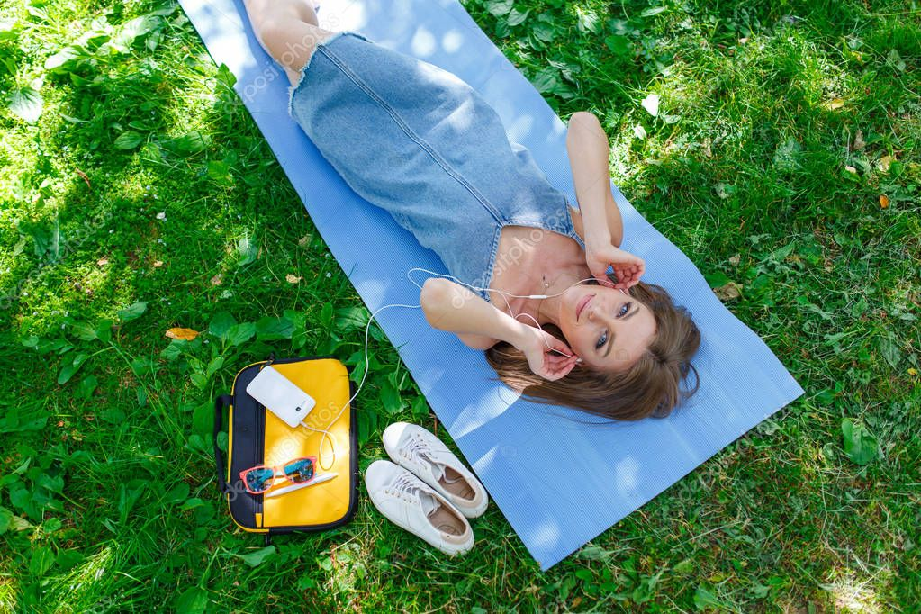 Woman relaxing on the grass in a park listening to music on her mobile phone. Top view