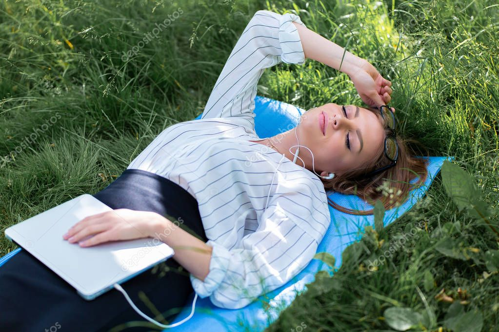 Woman resting in the park lying on the grass with a laptop and listening to music