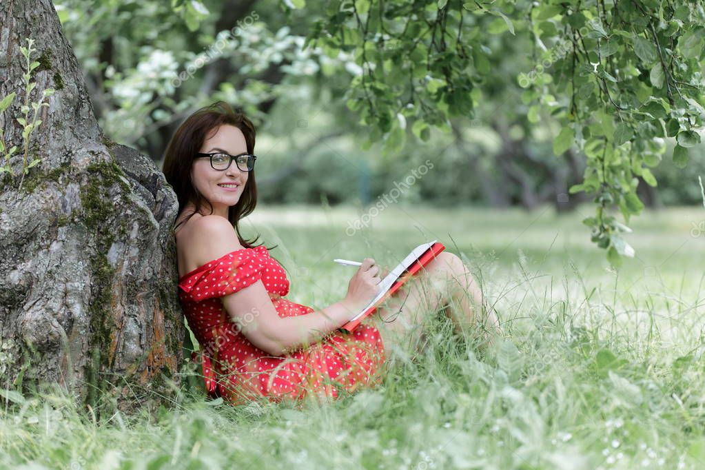Young woman sitting on grass under tree and writing notes