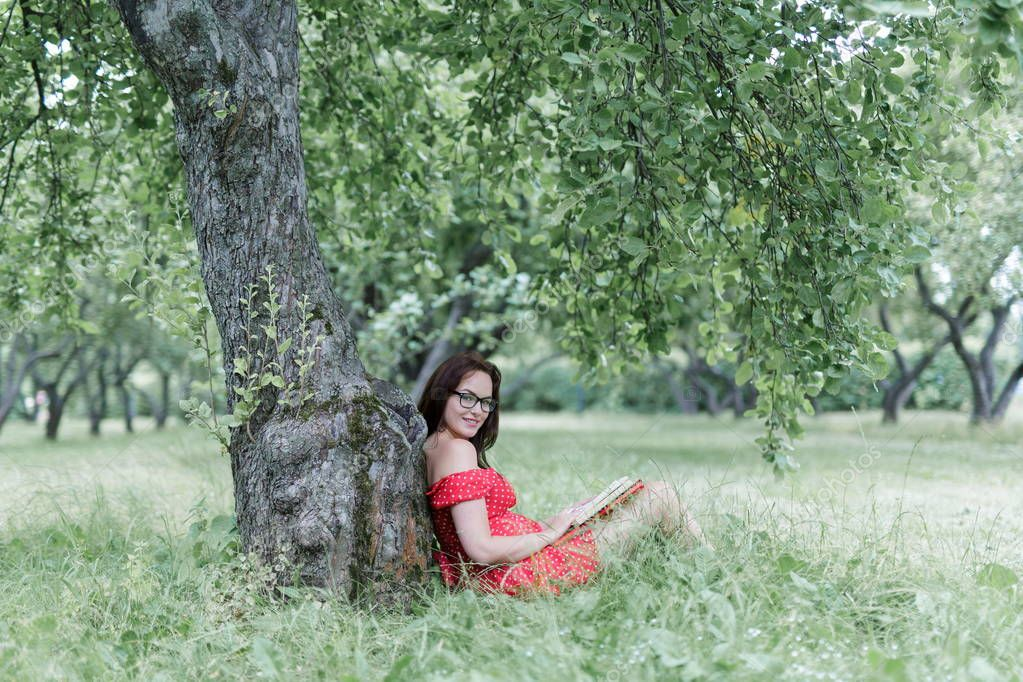 Young woman sitting on grass under tree and reads a book