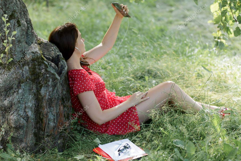 Young woman sitting on grass under tree with her smartphone and takes selfie