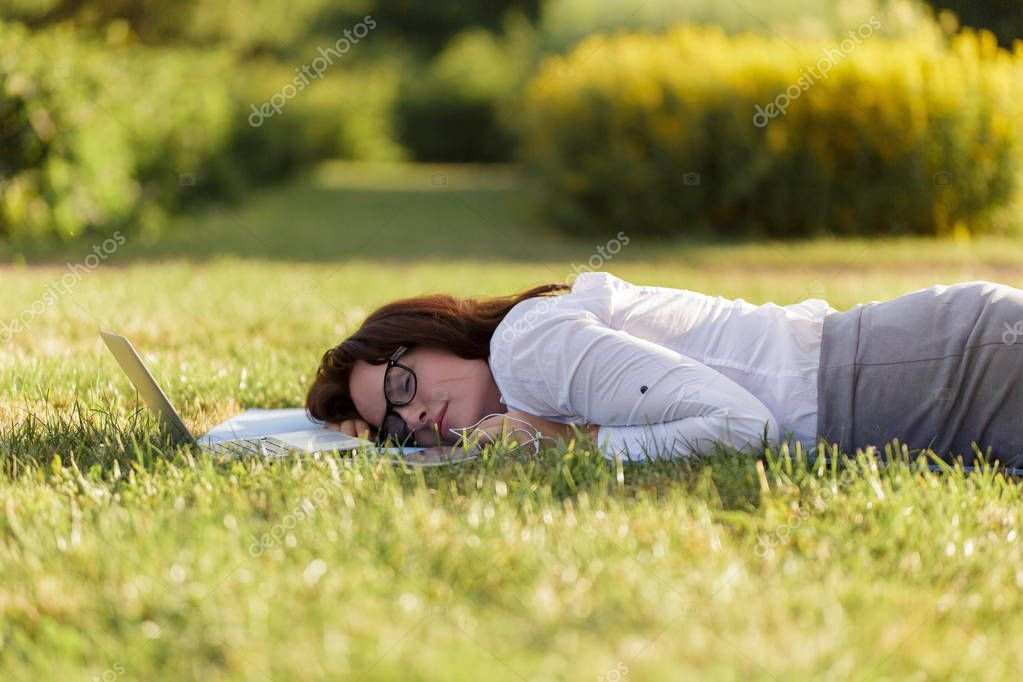 Business girl lying on a green grass and sleeping next to her laptop.