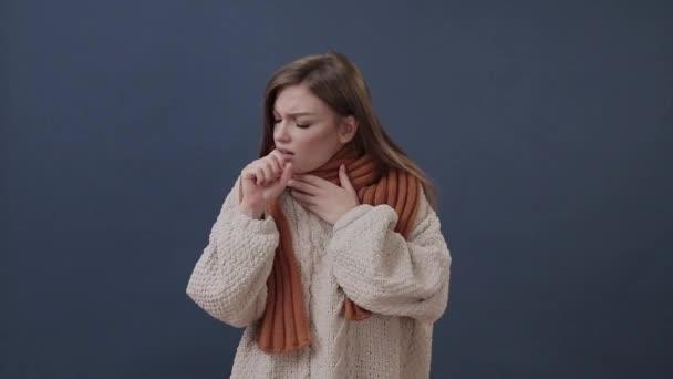 Krankes Mädchen in einem warmen Schal mit Nase und Kopfschmerzen eingewickelt