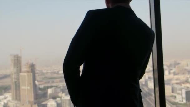 Businessman in a suit looks out of a big window in a city on a sunny day. Stock. Man in casual suit stay arms akimbo against bright window in living room, black silhouette