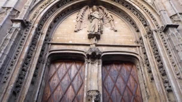 Sculptures and antique artistic reliefs on the gates. Stock. Sights and monuments of medieval Europe. Entrance with big gates of catholic cathedral with statue. baroque and renaissance style.