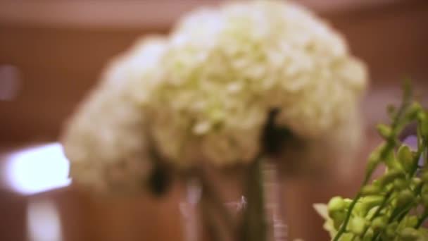 Detail bílé květy. V UK. Dovolená květiny ve váze. Květinové dekorace na svatební stoly