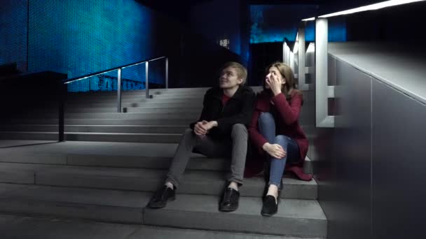 Young couple sitting on stairs at night. Beautiful night for a walk around the city