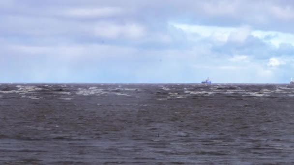 Tanker ship at sea during a storm  Tanker cargo ships on the horizon under  an overcast sky  A dark cloud of stormy sky with a cargo ship and waves in  the sea  Video