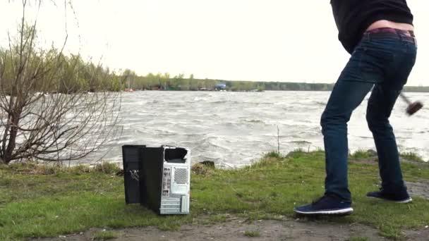 Muž rozbije počítač jednotku systému kladivo. Muž s kladivem saní a ničí počítač pomalý pohyb, řeky a lesa pozadí. Koncept konfrontace mezi přírodou a technologický pokrok