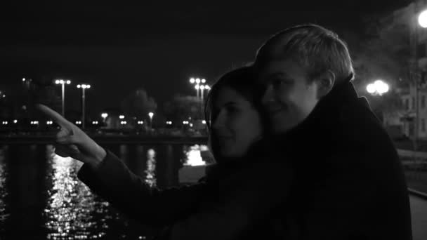 A couple in love stands against the lights of a night city at waterfront. Amazing wedding couple near the river at night, monochrome