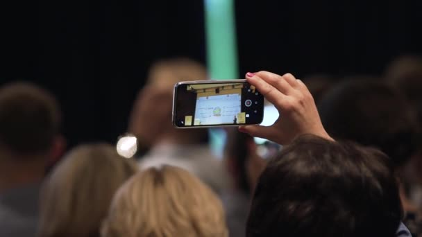Close up of recording video with smartphone at event. Stock. Human hands shoot video on the phone