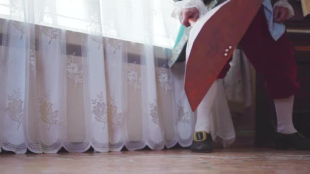 Hudebník ve starých šatech konce balalajka. V UK. Konceptuální retro záběry