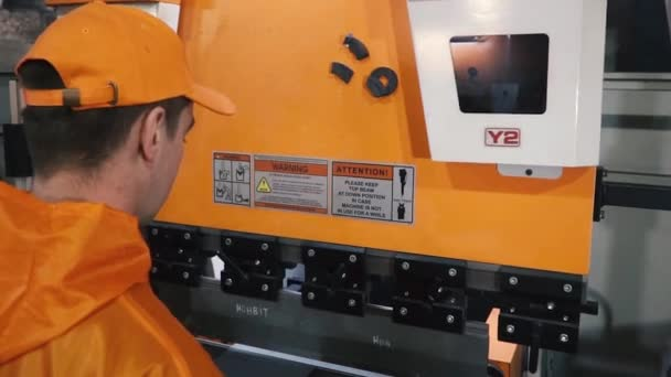 Worker in factory at metal skip machine putting work piece in. Clip. Man working with sheet metal and special machine tools for bending