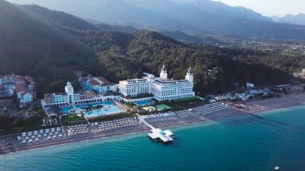 Pohled shora domů na palm beach, bazén a loď poblíž dřevěné molo. Video. Pohled shora na luxusní resort na pláži