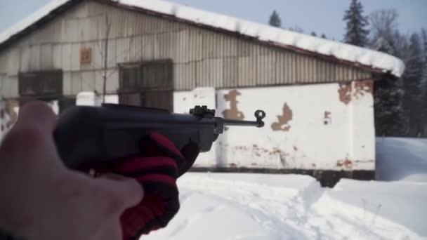 Egy ember, egy pellet fegyvert felé a cél, célja, hogy a téli a gyakorló. Klip. A lövő az álcázás a puska egy optikai látvány, a hangsúly a fegyverek cél célok