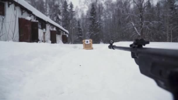 Egy ember, egy pellet fegyvert felé a cél, célja, hogy a téli a gyakorló. Klip. A lövő az álcázás a puska egy optikai látvány, a hangsúly a fegyverek cél célok.