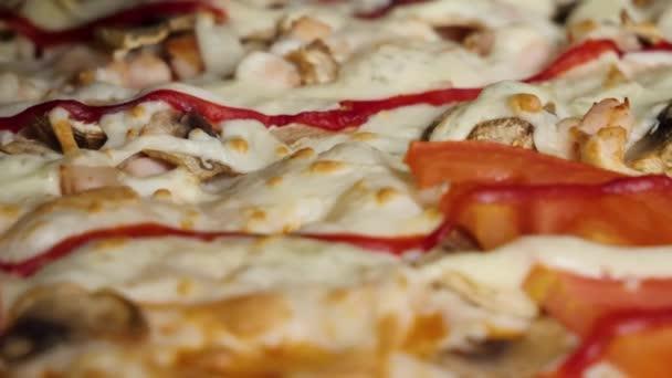 Zblízka pizzu. Rám. Pizza, předení na talíři. Pizza na pozadí. Velká Italská pizza s černými olivami, slanina, salám a sýr detailní zobrazení