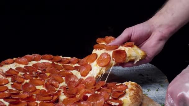 Momento del pasto in pizzeria, uomo che prende una fetta di pizza girato con profondità di campo molto sottile. Telaio. Taglio fetta di pizza a mano e prenderlo, primi piani, colpo a macroistruzione. Pizza e fetta di pizza in mano nella