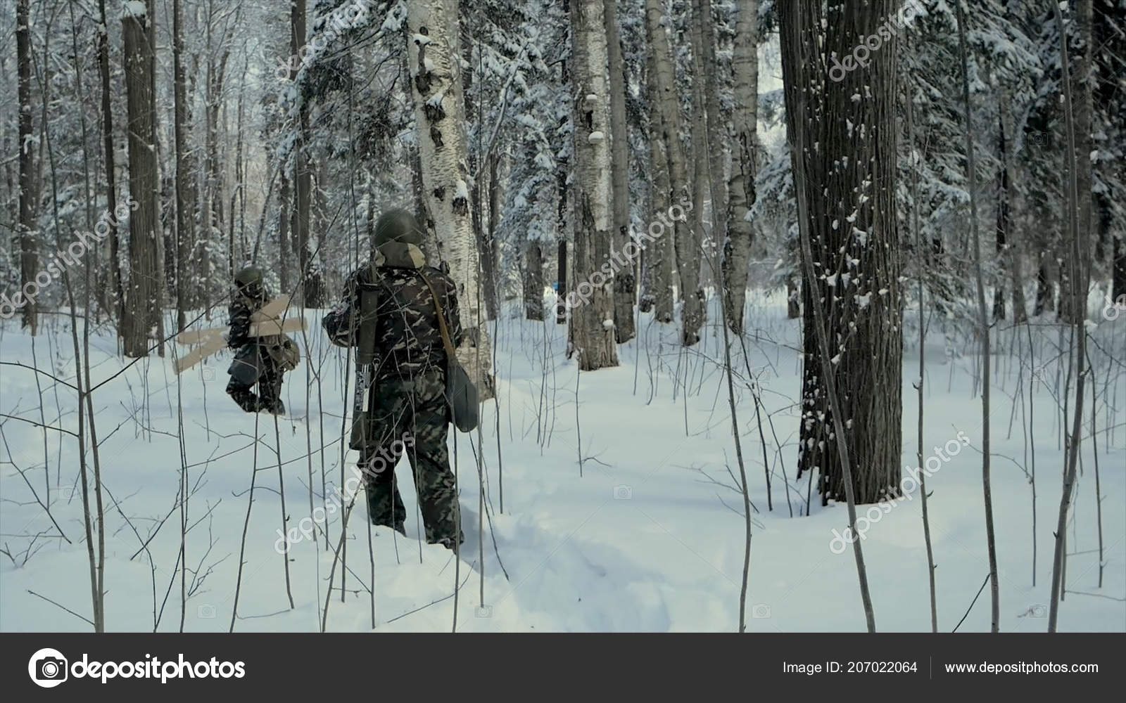 Soldier with weapons in cold forest  Winter warfare and