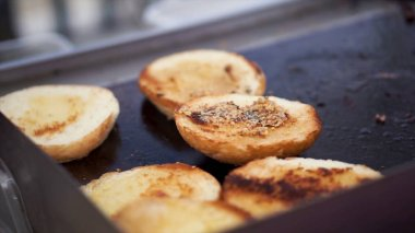 Potatoes prepare on a grill. Clip. Baking potatoes on the grill, the cook lubricates the potatoes with sauce. Hand Using Tongs For Turning potatoes on the Barbecue.