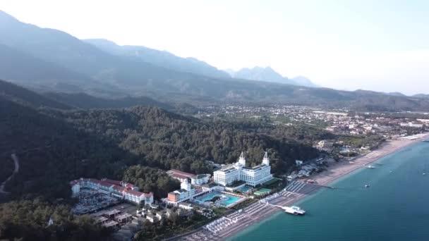 Vista aerea sul litorale, con Hotel di lusso con cielo blu e sfondo foresta e le montagne. Video. Vista superiore bella estate bianco dellalbergo di lusso sul mare di costa con montagne, foreste e cielo