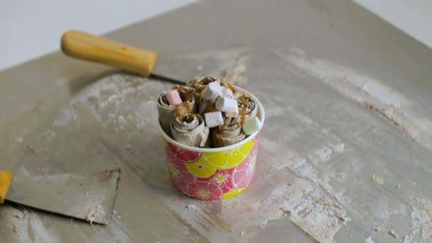 Vaření přírodní ovocné zmrzliny v thajském stylu. Klip. Výroba zmrzliny rohlíky s kokosy na studený talíř. Výroba zmrzliny rolích na studený talíř. Zblízka. Thajském stylu hýbat-se smažil válcované zmrzlina