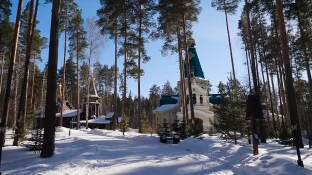 Zimní krajina s zasněžené stromy na pozadí křesťanské církve po sněhu. Mrazivý slunečný den