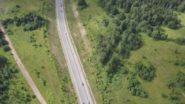 Letecký pohled na dálnici se stromy a hory. Klip. Pohled shora z asfaltové silnici v lesnaté oblasti