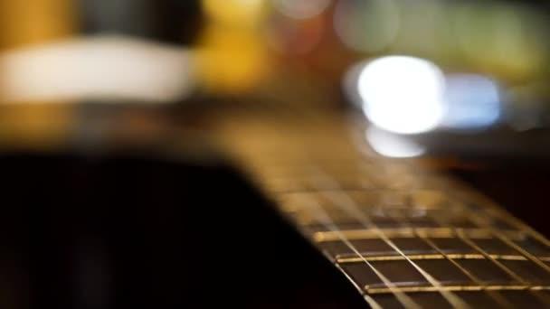 Akustická kytara most a smyčce zblízka. Detail z kytarových strun. Elegantní kytara