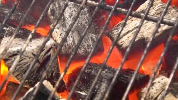 Pohled na horké hořící uhlí brikety zářící v Pit Bbq gril. Spalování uhlí pro vaření jídla na grilu. Detailní záběr