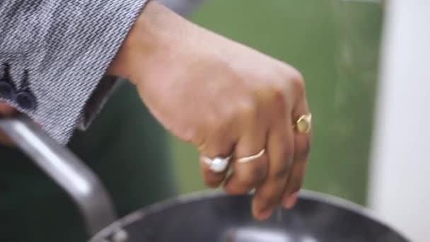 Detailní záběr z rukou šéfkuchaře, posypat kořením na nádobí v kuchyni. Klip. Šéfkuchař připraví jídlo. Posypeme salát s kořením. Vaření. Profesionální kuchyně
