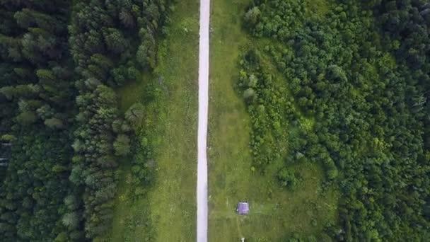 Letecký pohled shora letní zelené stromy, řeky, silnice v lese na pozadí. Letecký pohled na křivolaké cesty od silnice na hoře. Klip. Letecký pohled na auta jedoucí na venkovské silnici v lese. Antény