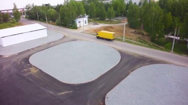 Vista aerea di Loading magazzino con camion Semi. Clip. Vista aerea superiore di camion con rimorchio carico in movimento sulla strada in direzione della superficie di magazzino di carico. Vista aerea di scarico camion