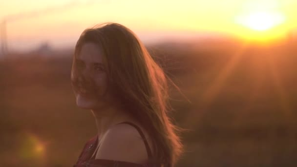 Amazing young woman with charming smile at sunset and sun glare. Charming woman smiling rays of sunset