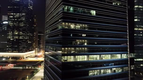 Vnější moderní mrakodrapy s svítící okny kanceláří megapolise večer. Střela. Pojetí života ve velkoměstě. Pohled shora kanceláří výškové budovy v centru města v noci