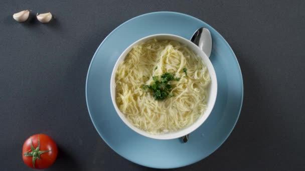 Kuřecí polévka s nudlemi na talíři. Scénu. Kuřecí nudlová polévka krémová barevné keramické mísy s úchyty. Sušenky a polévková v pozadí.