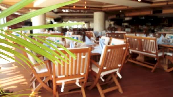Interiér letní restaurace. Scénu. Pastelových kavárna. Prázdné venkovní kavárna - kovový kovaný nábytek ohrazené zelený živý plot. Stoly a židle v restauraci terrace. Staromódní café terrace