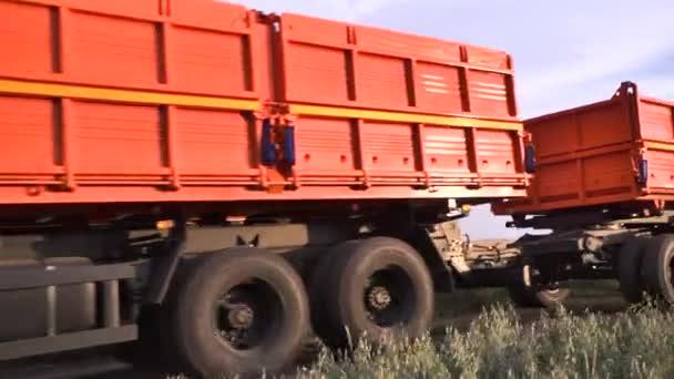 Vůz jde na venkovské silnici podél zemědělská pole. Scénu. Detail kolem oranžové náklaďák s přívěsem na venkovské silnici v poli