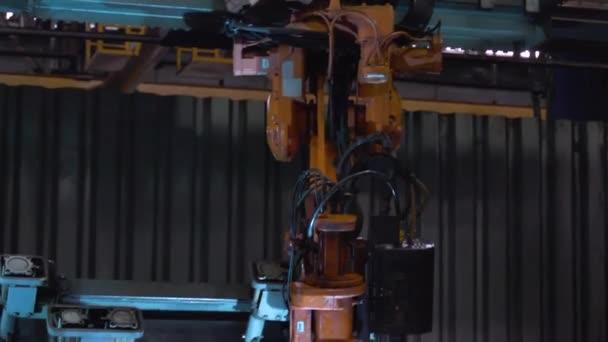 zblízka robotické svařování v továrně. Scénu. Průmyslový robot oranžové svářeč provádět svařování kovových částí. Detail podrobnosti o robot svářečka během provozu